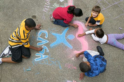 Kids Drawing the CASA Logo with Sidewalk Chalk