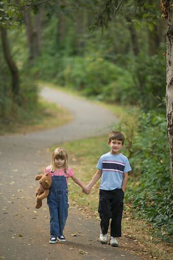 Little Boy and Girl Holding Hands Walking Down a Road