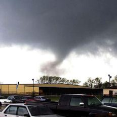 Funnel cloud in the distance with parking lot in the foreground